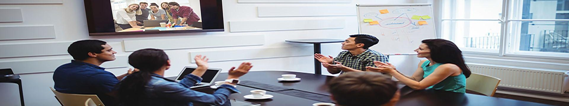 Business executive applauding during a video conference in the conference room